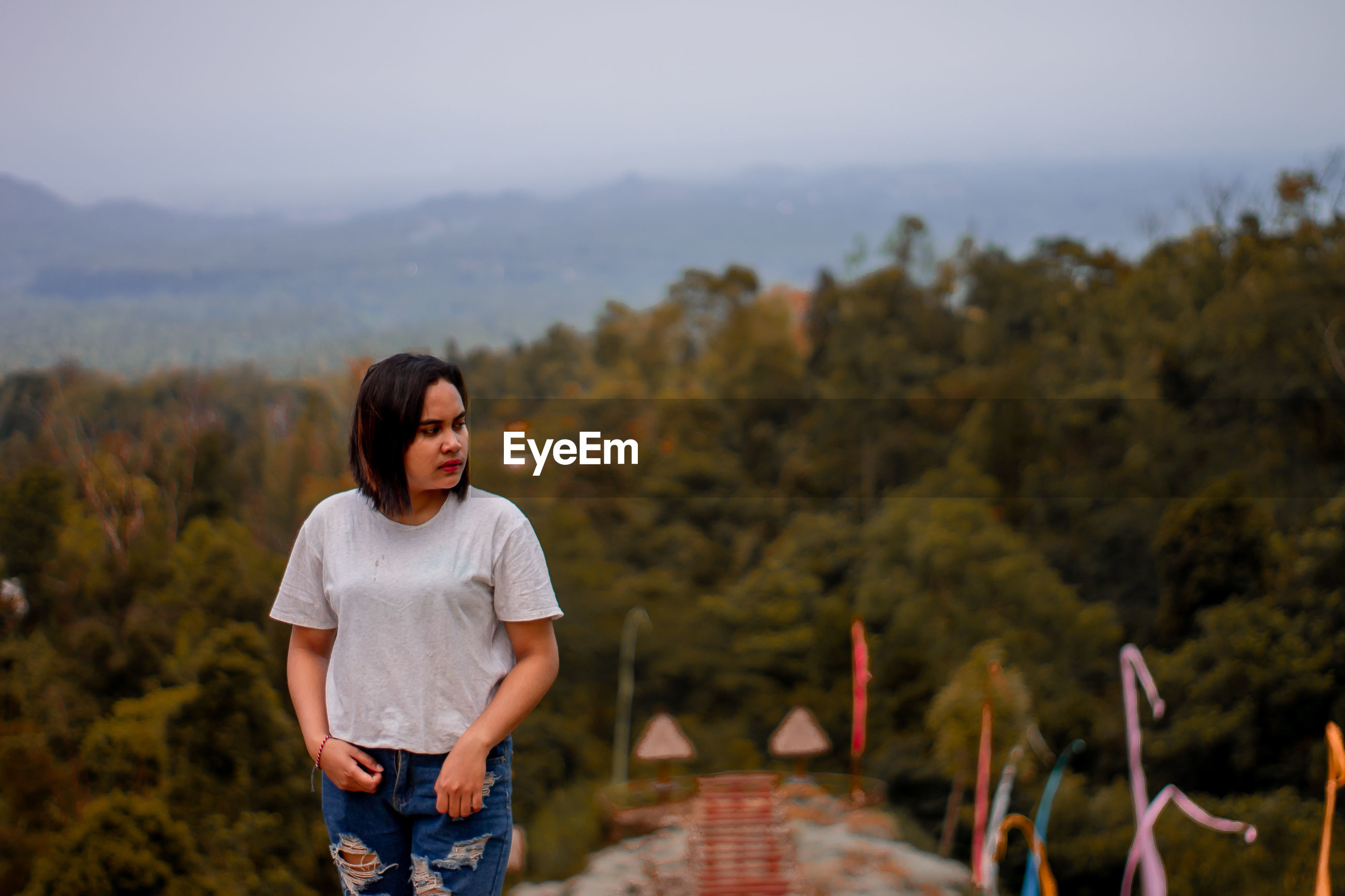 Young woman standing on observation point against sky