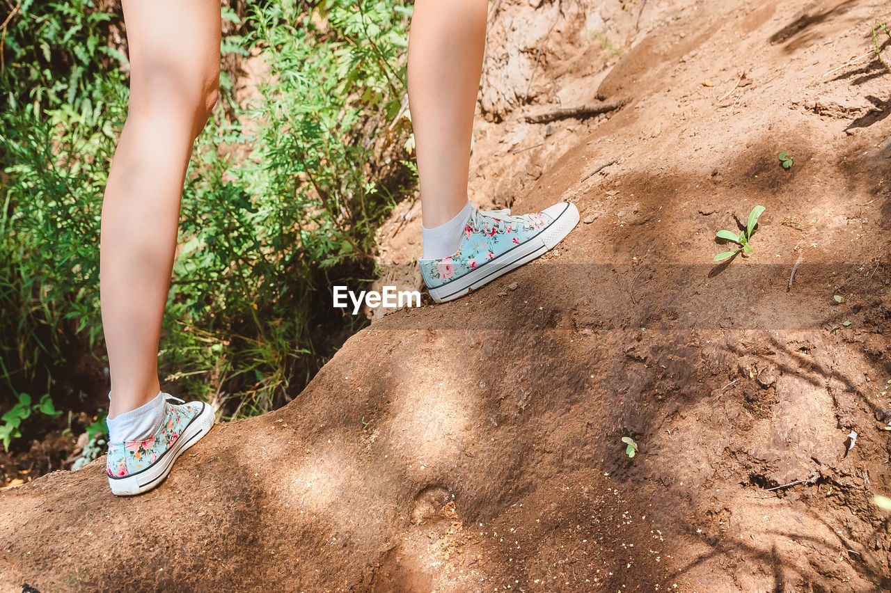 A girl in sneakers goes up the mountain. feet close-up on a hike in the wilderness