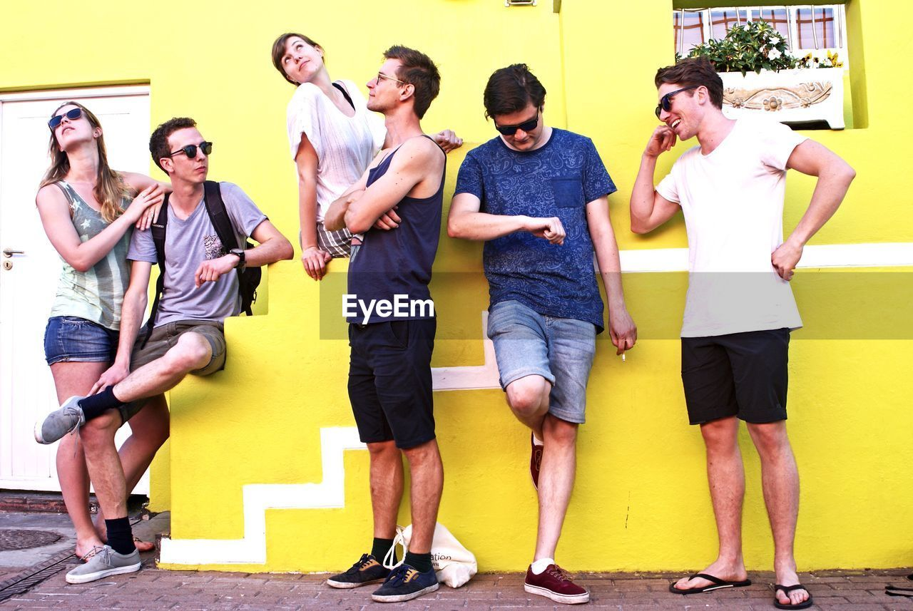 full length, casual clothing, yellow, lifestyles, young adult, real people, front view, standing, young men, togetherness, leisure activity, friendship, happiness, day, young women, outdoors, men, smiling, building exterior, adult, people