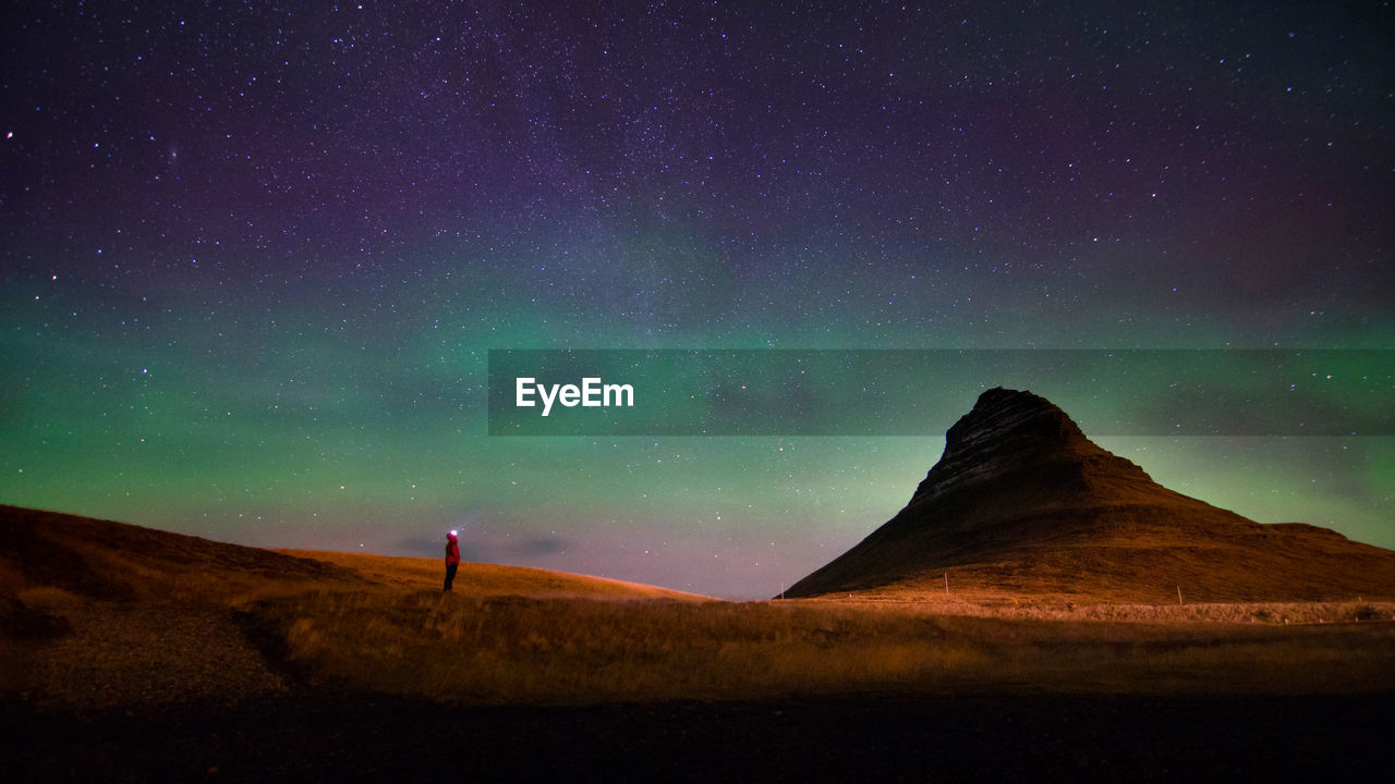 Scenic View Of Aurora Borealis Above Kirkjufell Mountain