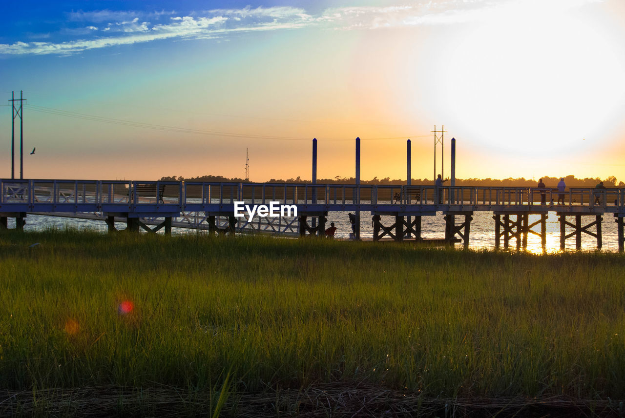 sunset, water, sky, sun, bridge - man made structure, grass, nature, outdoors, growth, built structure, beauty in nature, no people, tranquility, field, tranquil scene, river, architecture, scenics, city, day