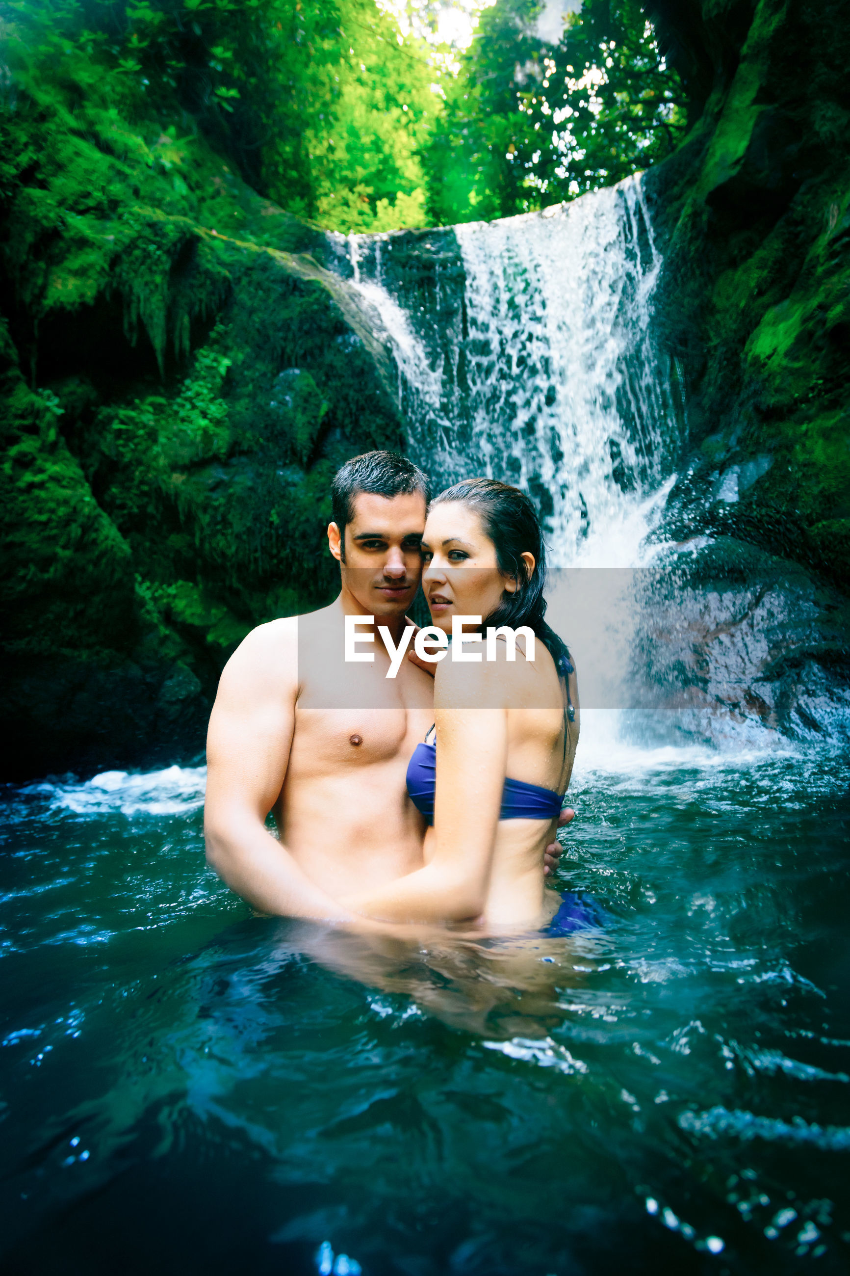 Young couple standing in river at forest