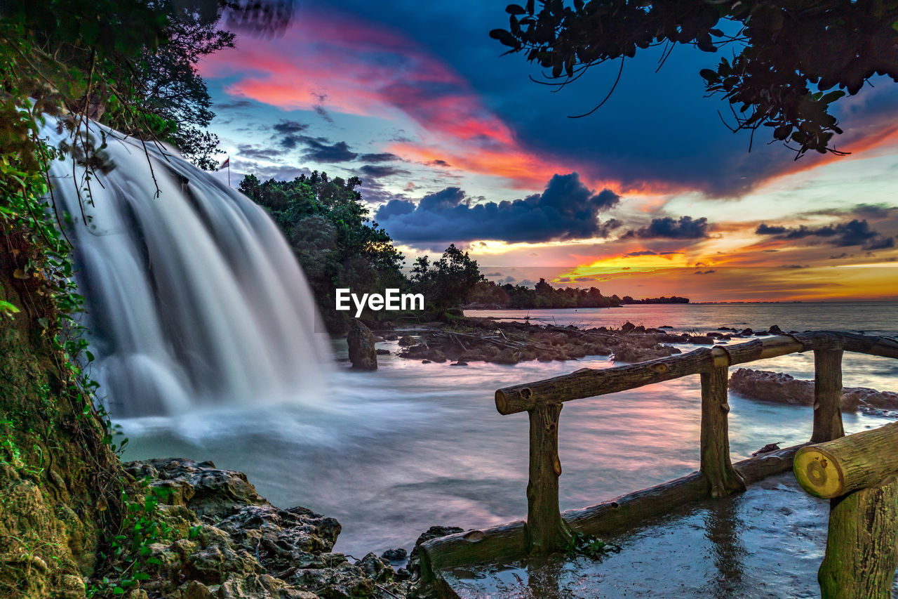 water, sky, scenics - nature, beauty in nature, sunset, motion, long exposure, cloud - sky, sea, tree, orange color, nature, tranquility, idyllic, plant, flowing water, no people, tranquil scene, waterfall, flowing
