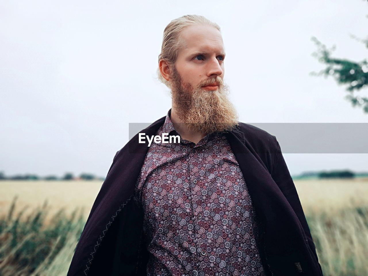 Low angle view of handsome bearded man standing on field against sky