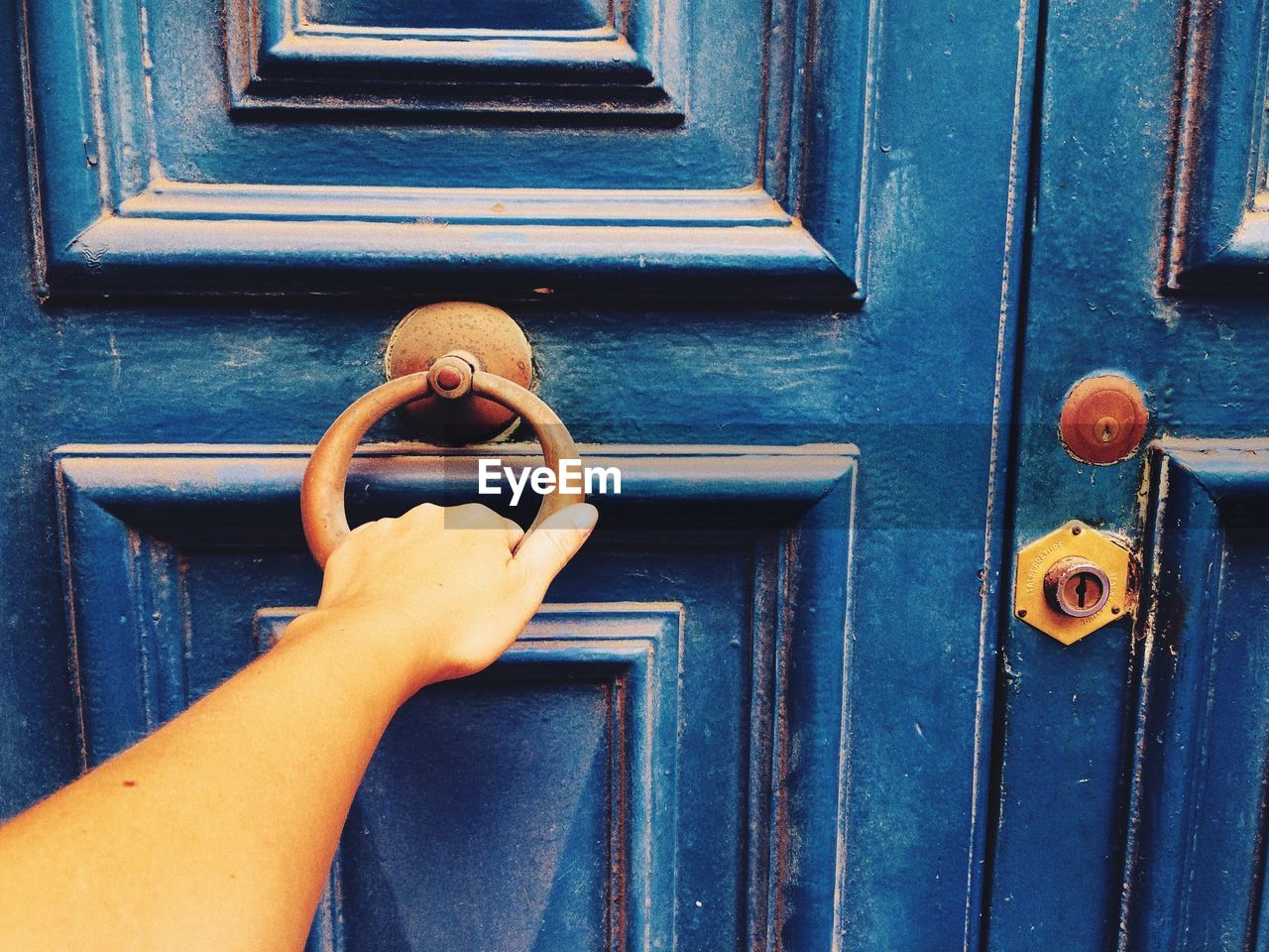 Cropped Hand Of Woman Knocking Door
