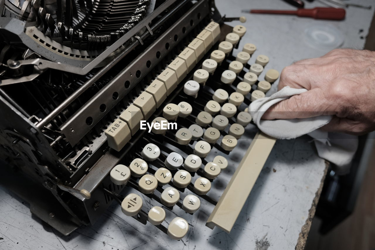 Cropped Image Of Man Cleaning Typewriter On Table