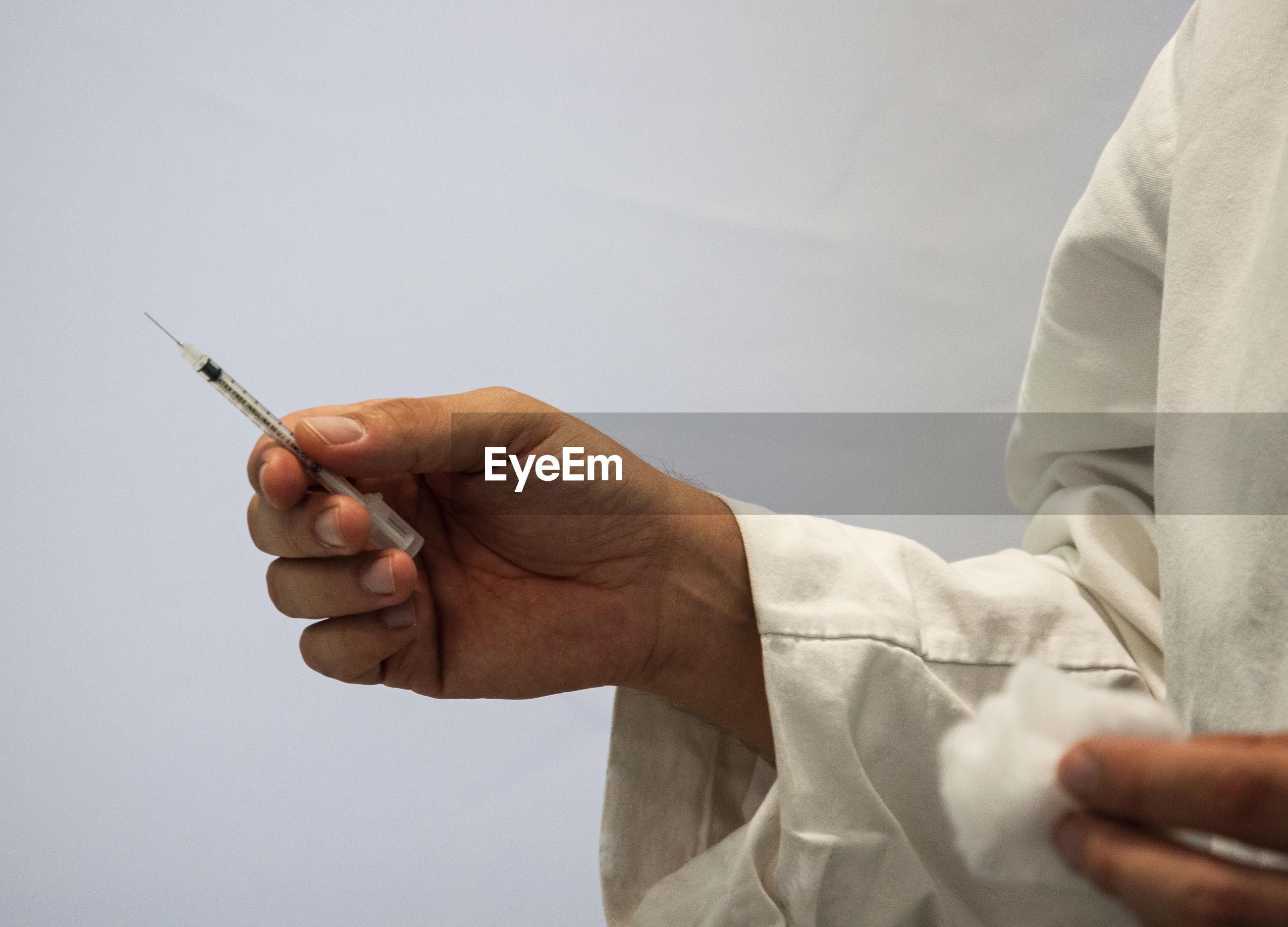 Cropped image of doctor holding syringe against gray background