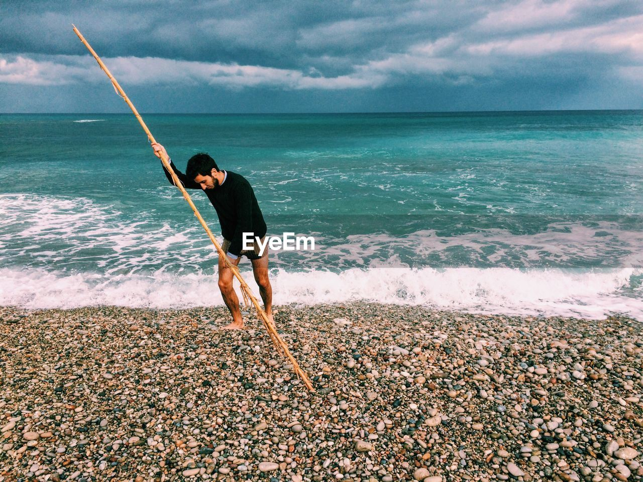 Fisherman with pole on seashore against cloudy sky