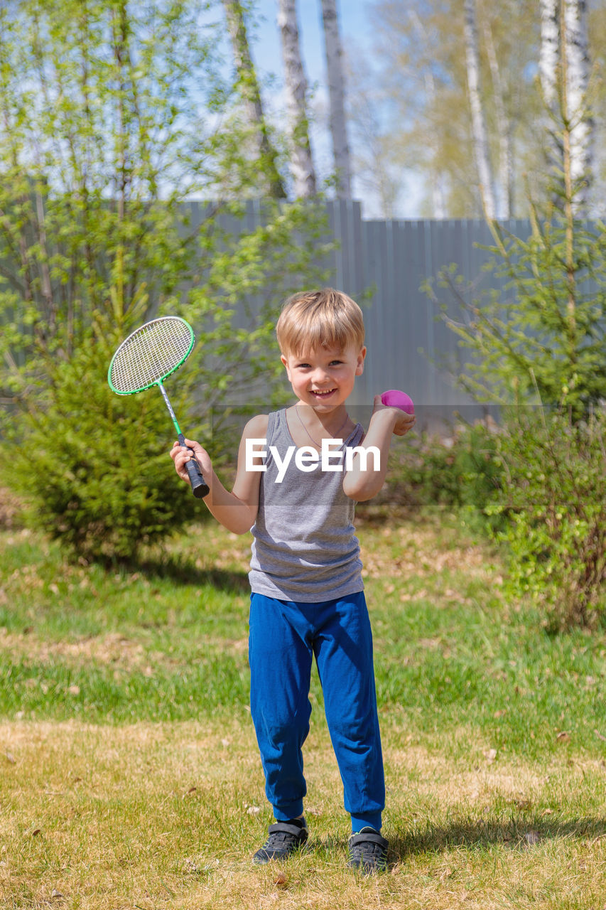 FULL LENGTH PORTRAIT OF SMILING BOY STANDING IN GRASS