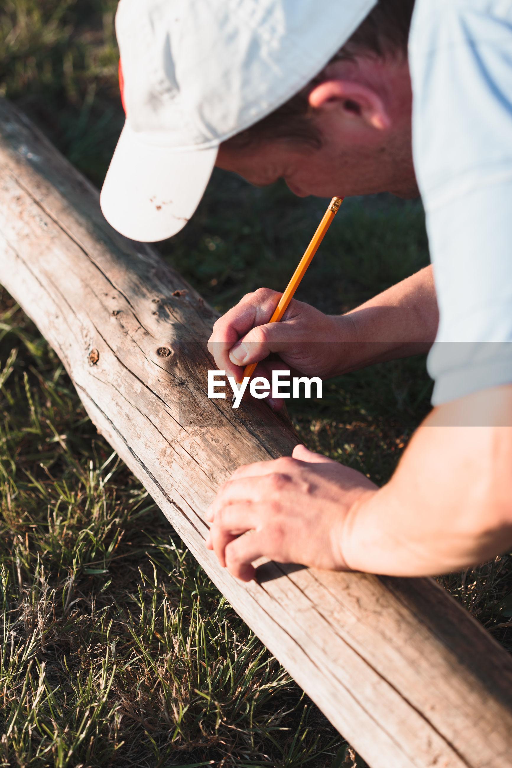 Man measuring wood and marking at field