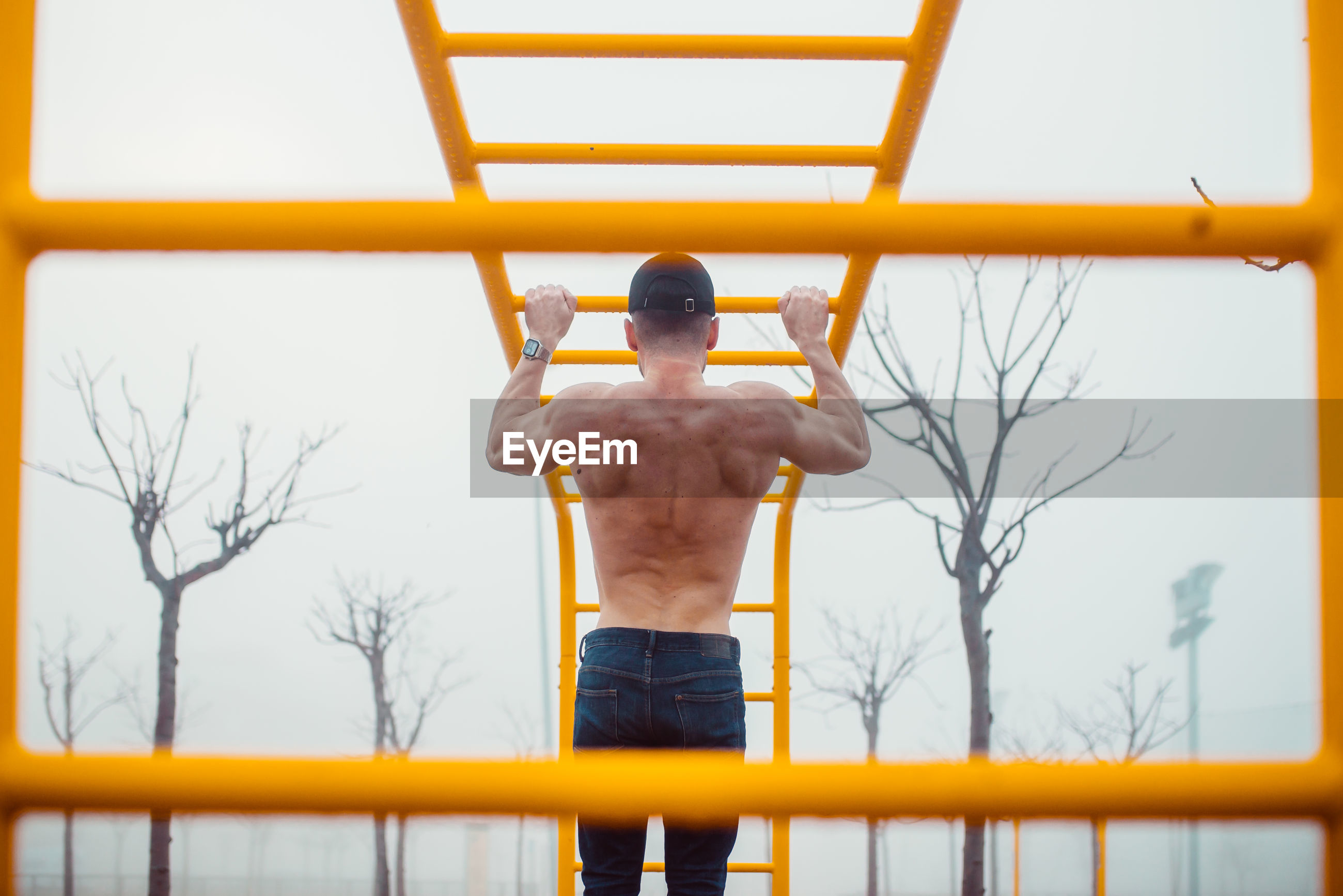 REAR VIEW OF SHIRTLESS MAN STANDING ON BUILDING