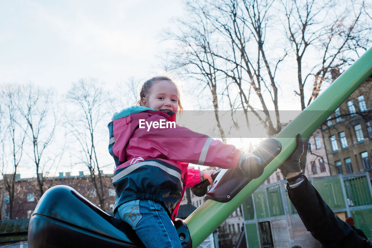 LOW ANGLE VIEW OF GIRL SITTING ON SLIDE