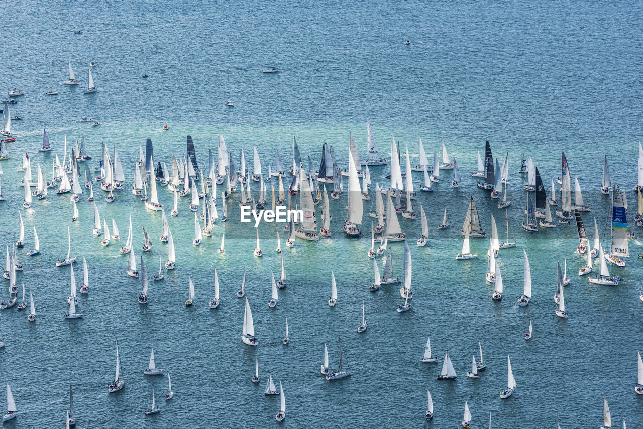 HIGH ANGLE VIEW OF SAILBOATS IN SEA BY BUILDING