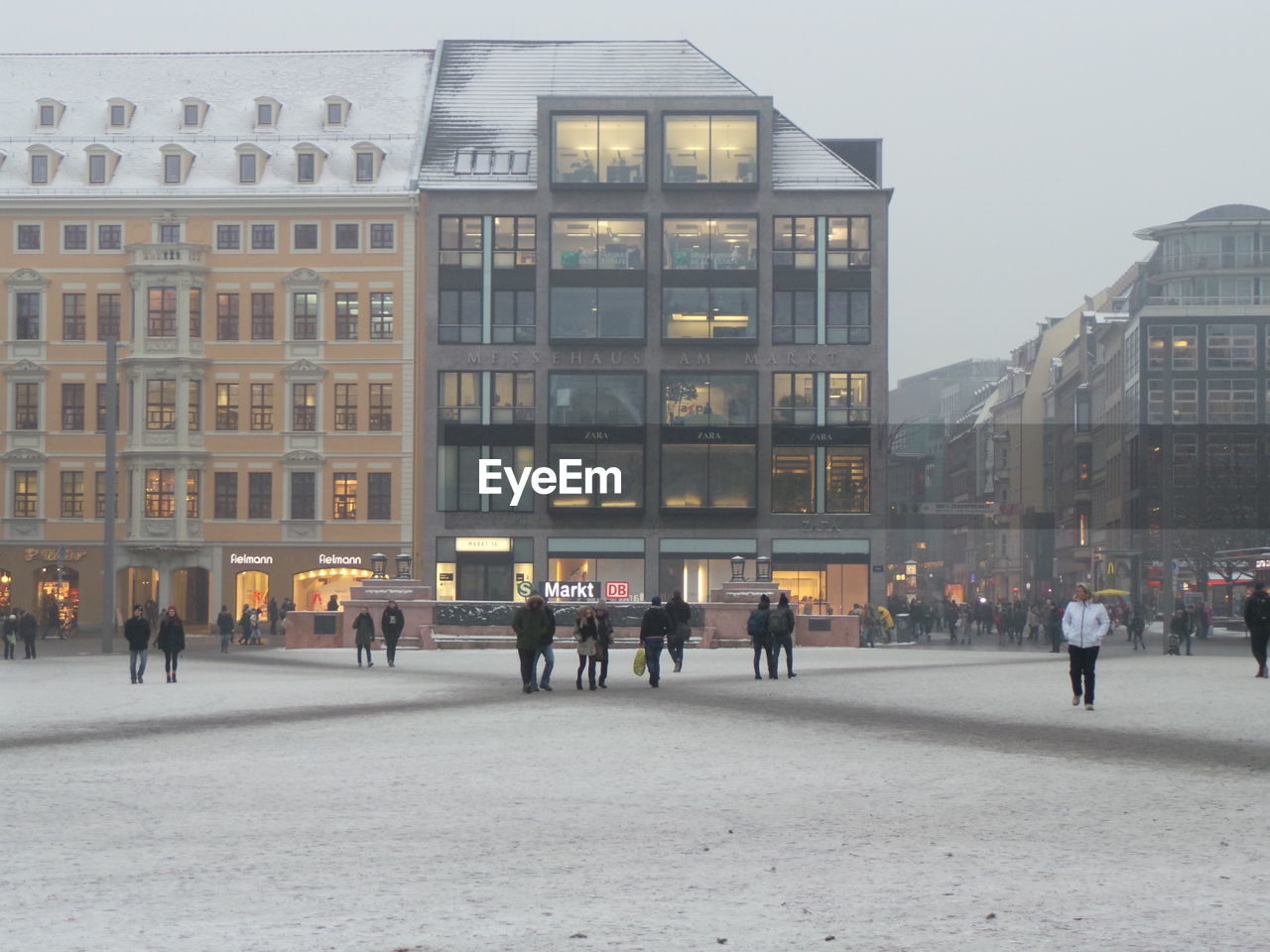 People walking on snow covered city street by buildings against sky