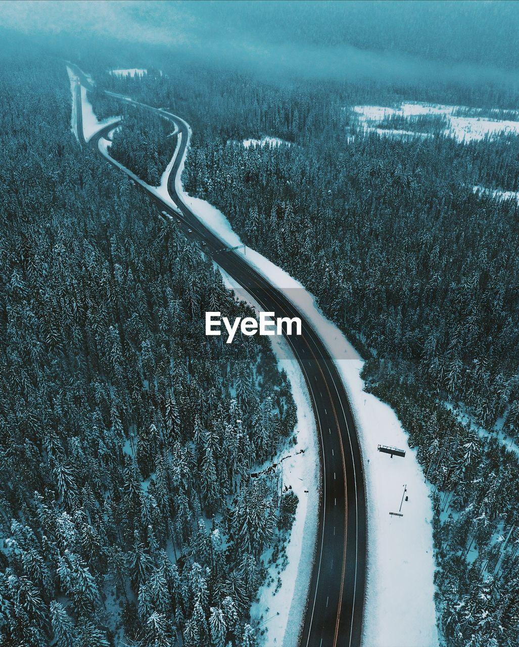 HIGH ANGLE VIEW OF SNOW COVERED ROAD