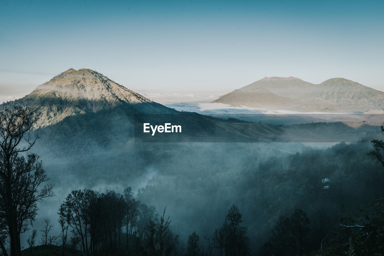 mountain, scenics - nature, beauty in nature, sky, tranquil scene, tranquility, tree, no people, non-urban scene, plant, environment, volcano, idyllic, nature, fog, landscape, mountain range, travel destinations, remote, outdoors, mountain peak, power in nature
