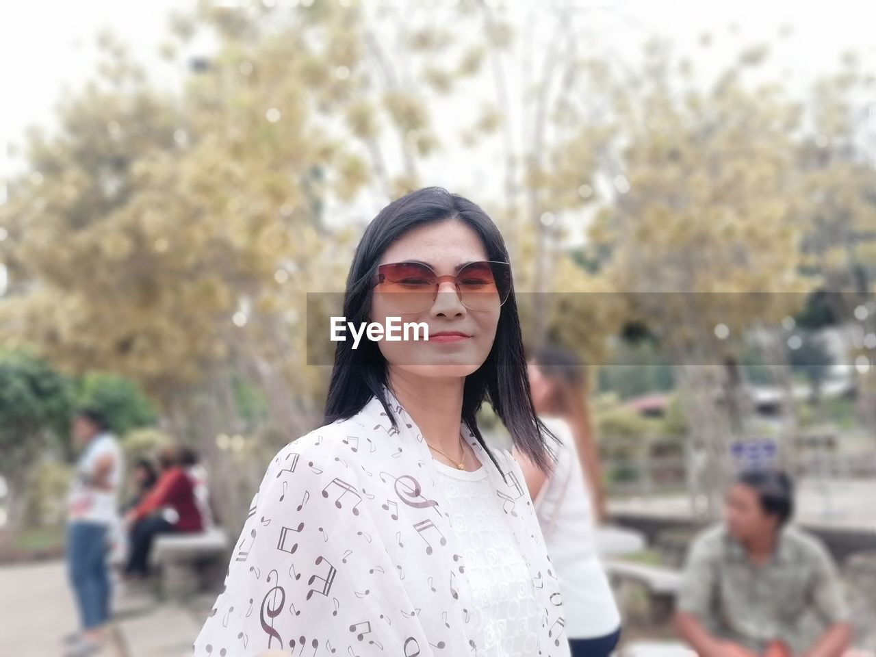 real people, focus on foreground, incidental people, young adult, lifestyles, one person, leisure activity, casual clothing, portrait, young women, glasses, front view, day, tree, hair, fashion, women, sunglasses, hairstyle, outdoors, beautiful woman, contemplation