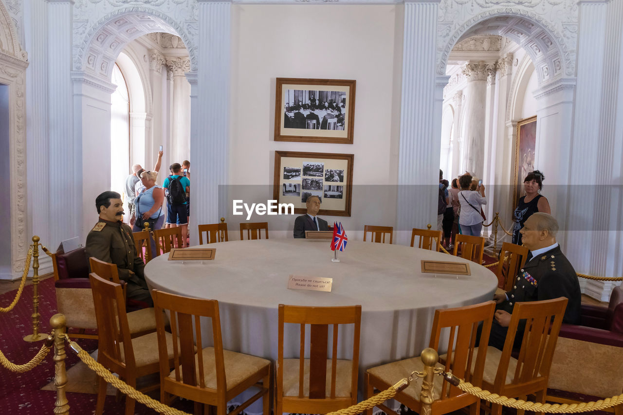 table, group of people, real people, seat, women, chair, men, architecture, indoors, adult, lifestyles, people, religion, belief, place of worship, built structure, sitting, spirituality, architectural column