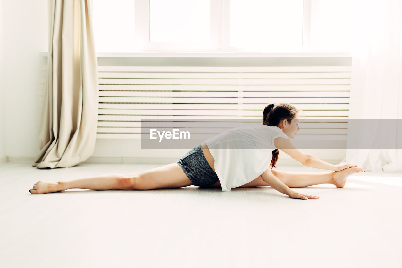 Full Length Of Young Woman Touching Toes While Doing The Splits At Home