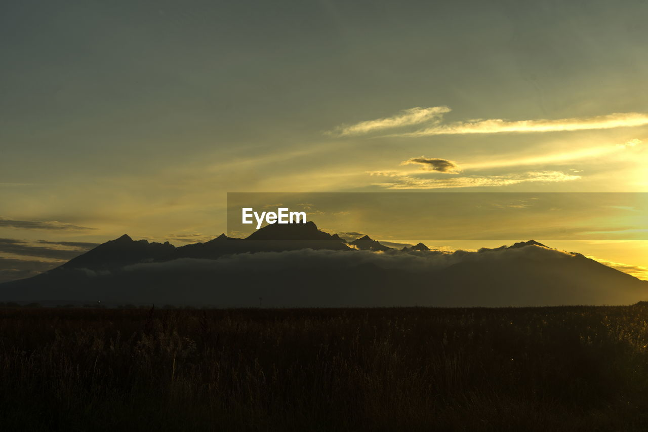 sky, scenics - nature, beauty in nature, mountain, tranquil scene, sunset, tranquility, cloud - sky, non-urban scene, environment, landscape, no people, idyllic, mountain range, nature, land, silhouette, outdoors, remote, plant, mountain peak