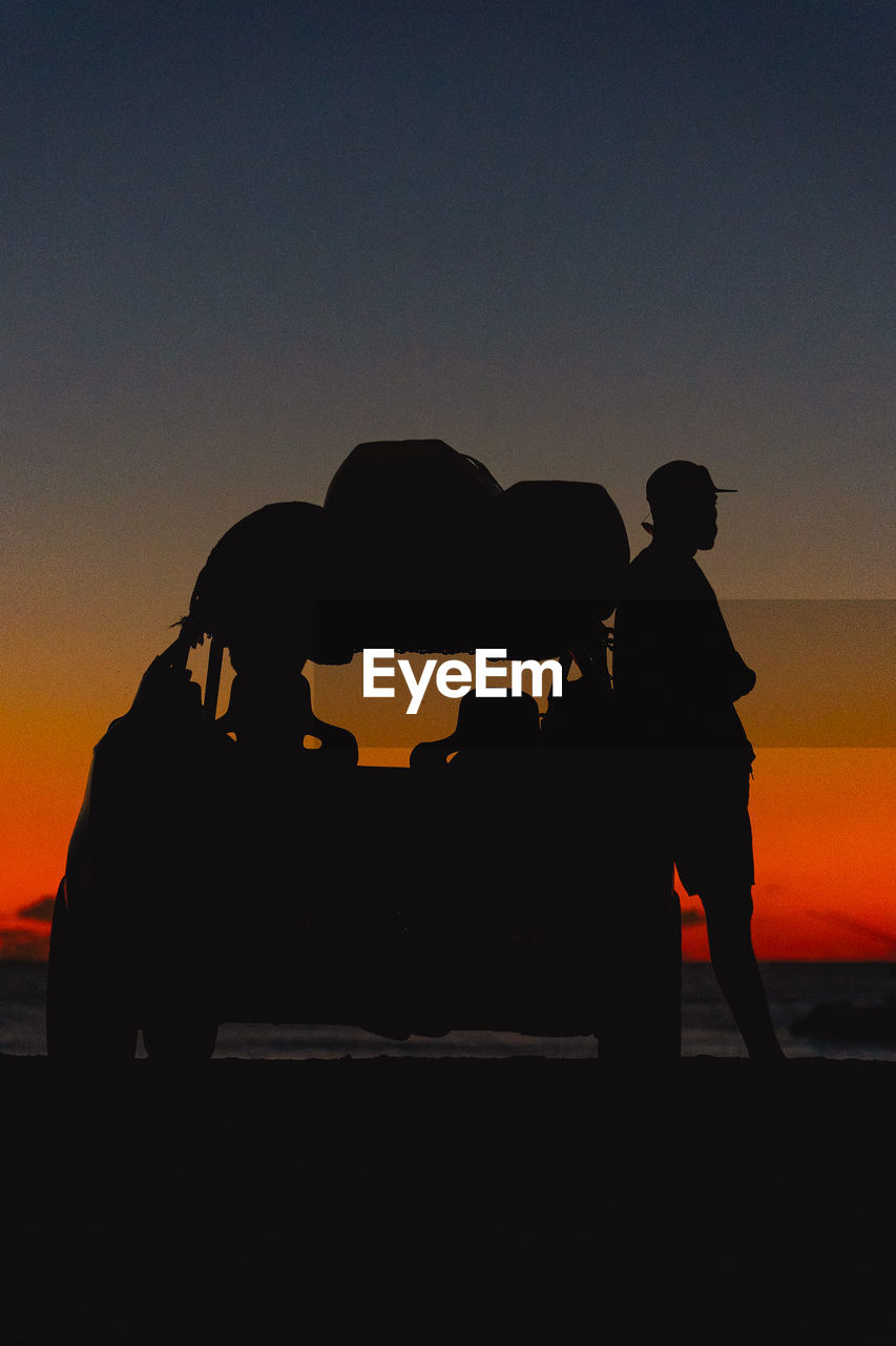 Silhouette man standing by off-road vehicle at beach against sky during sunset