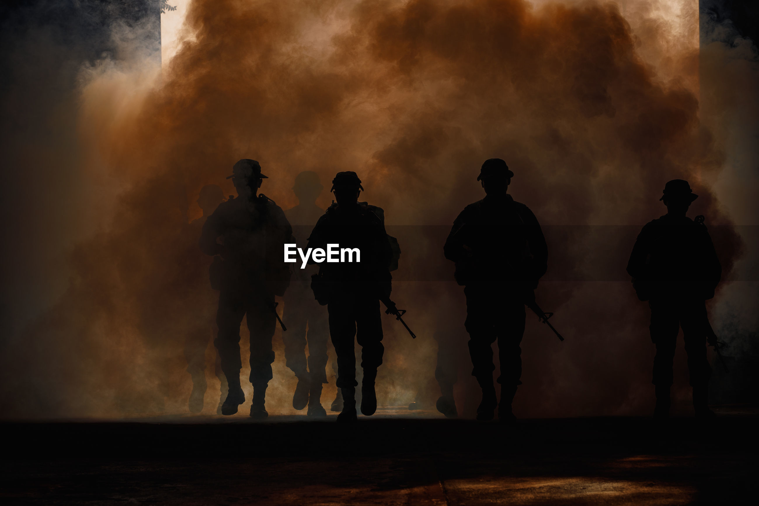 Silhouette army soldiers amidst smoke at sunset