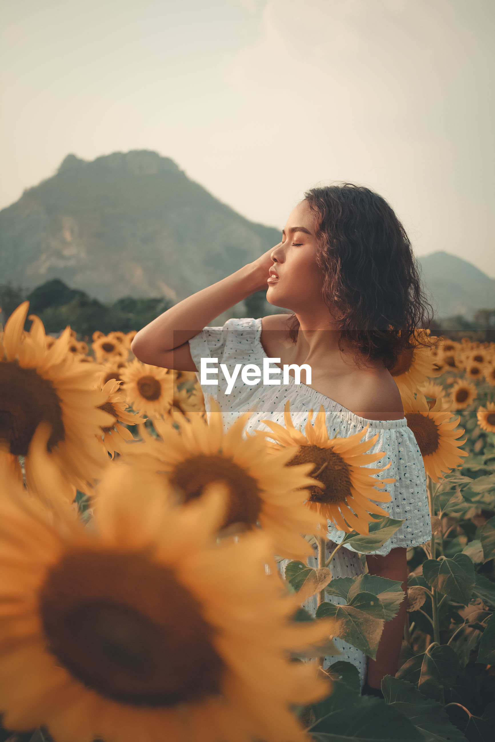 Young woman standing at sunflower farm against sky