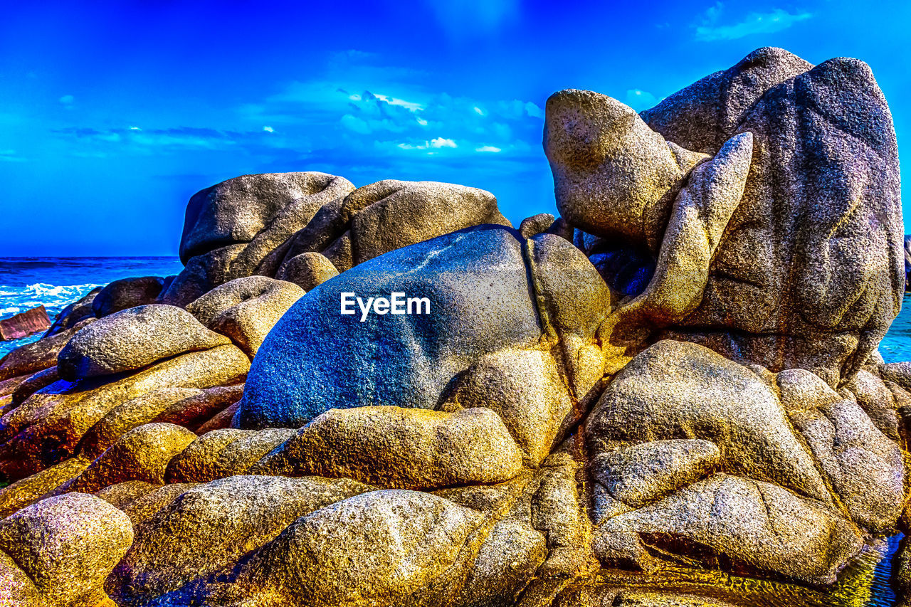 sea, sky, water, solid, rock - object, rock, blue, nature, beach, beauty in nature, land, no people, day, horizon, horizon over water, tranquility, cloud - sky, scenics - nature, sunlight