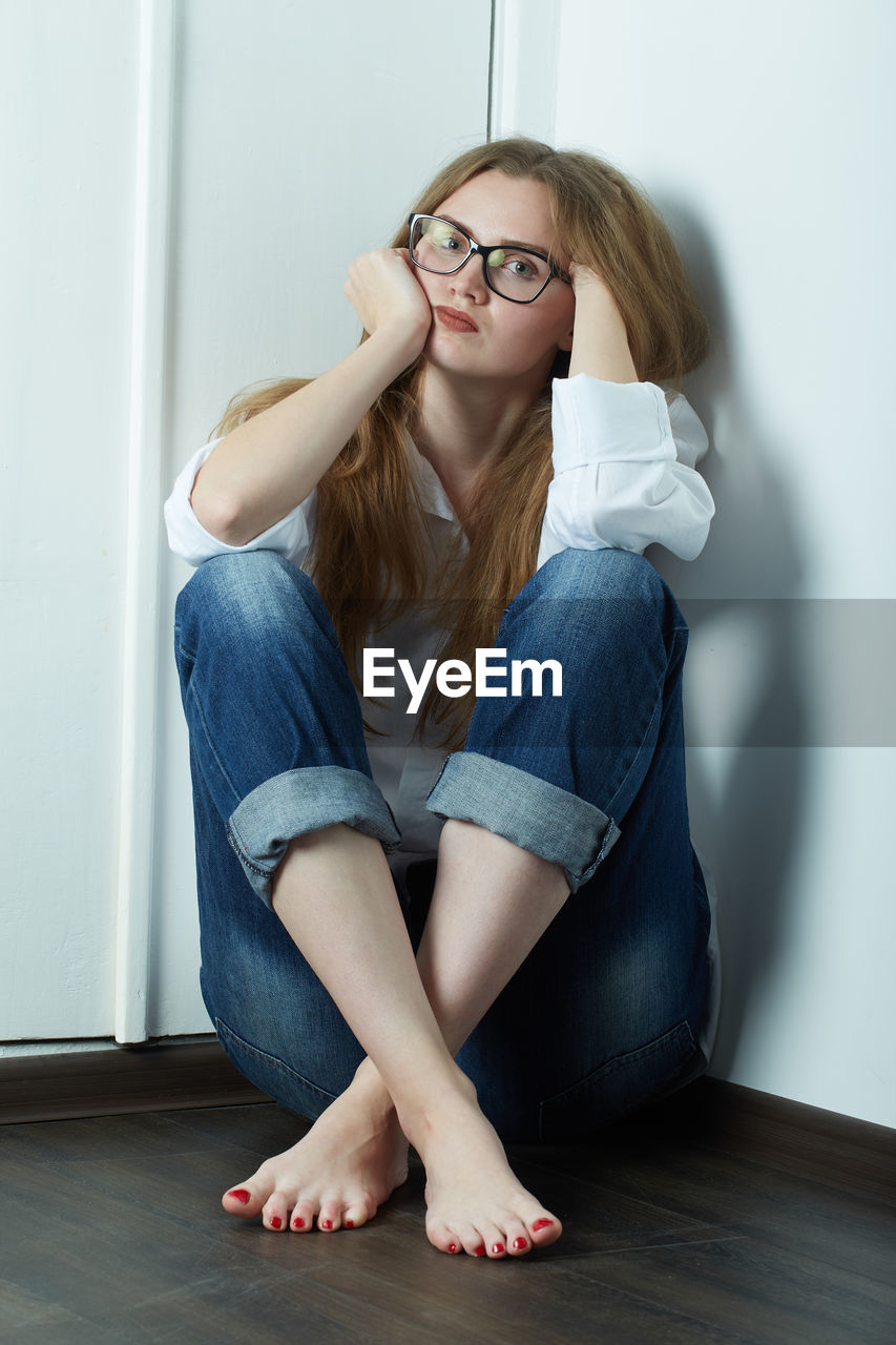 BEAUTIFUL YOUNG WOMAN SITTING WITH EYEGLASSES