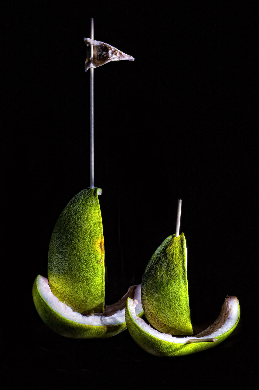 Close-Up Of Limes Hanging Against Black Background