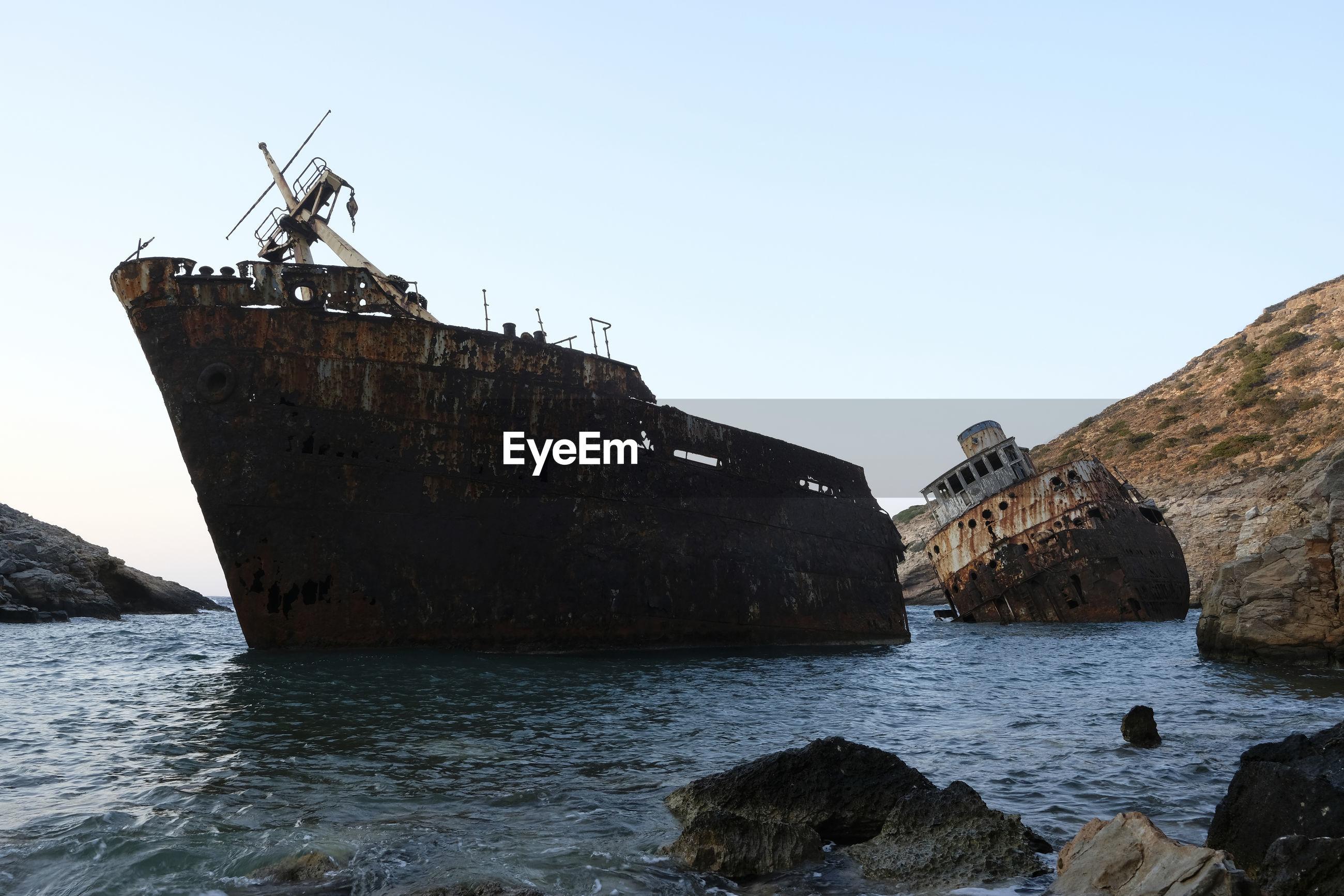 Shipwrecks in sea against clear sky