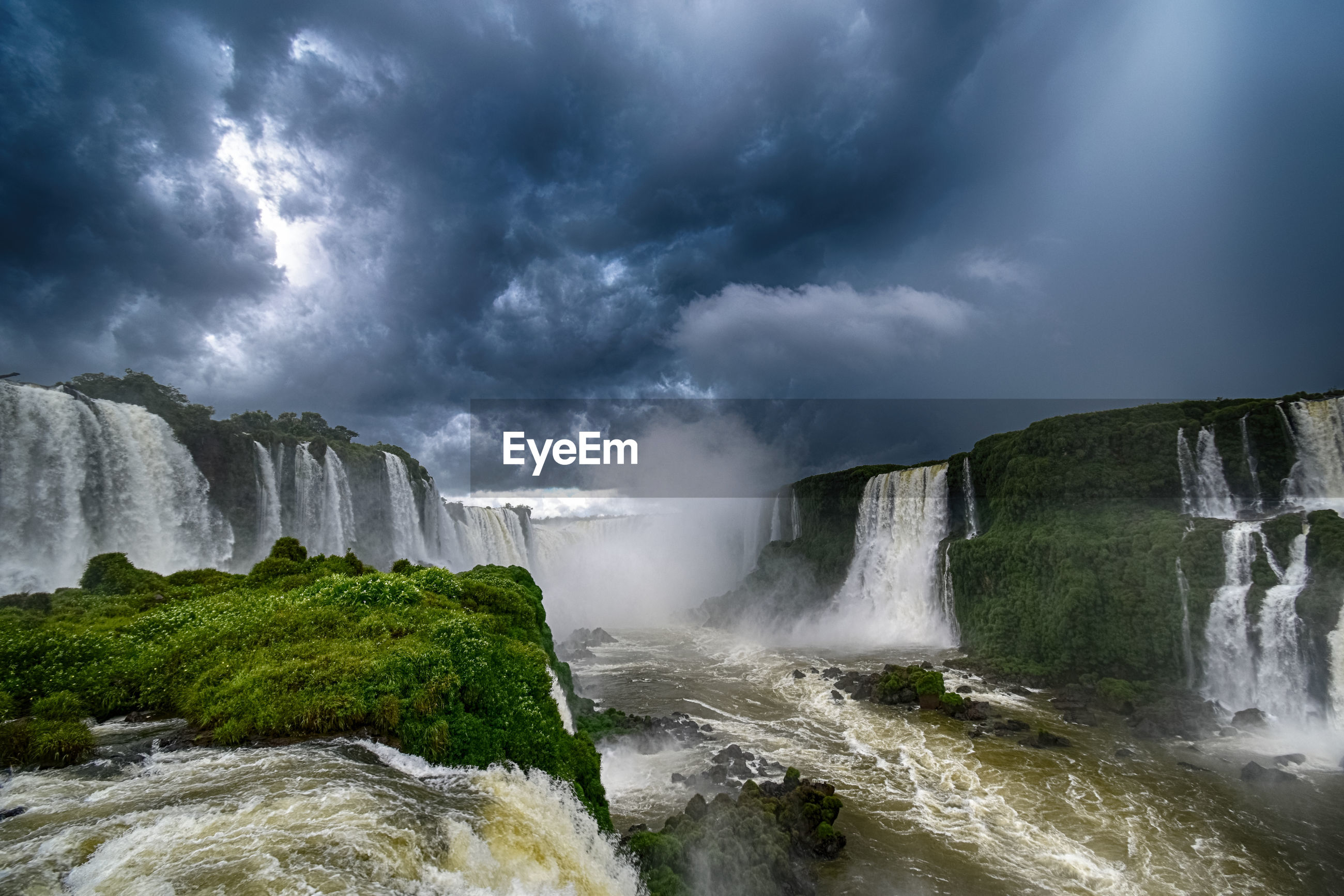 Panoramic view of waterfall against cloudy sky - cataratas do iguaçu