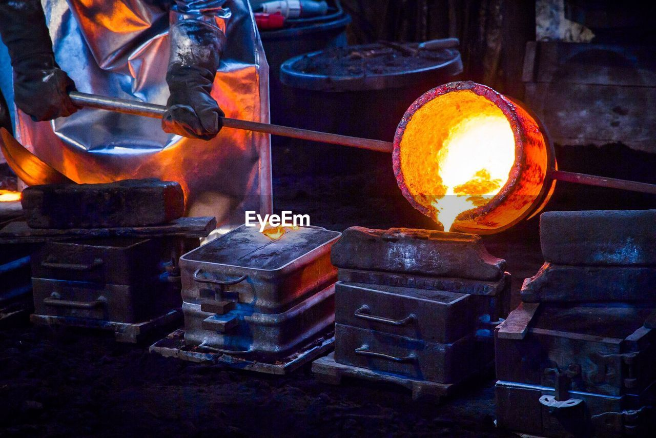 Midsection Of Worker Pouring Cast Iron In Container At Still Mill