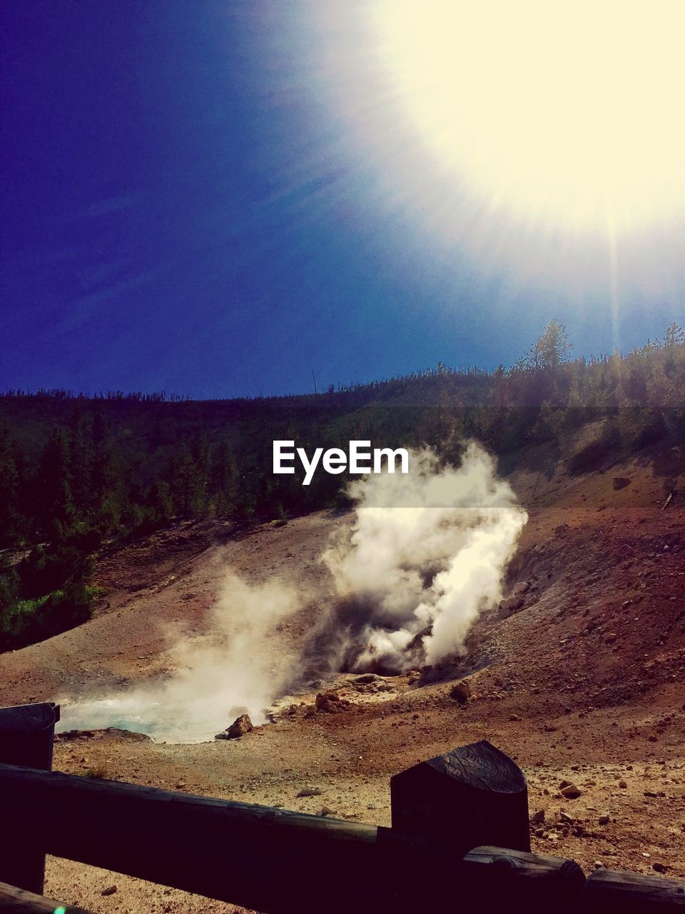 smoke - physical structure, landscape, nature, sunlight, outdoors, no people, sky, beauty in nature, scenics, day, clear sky, mountain, tree