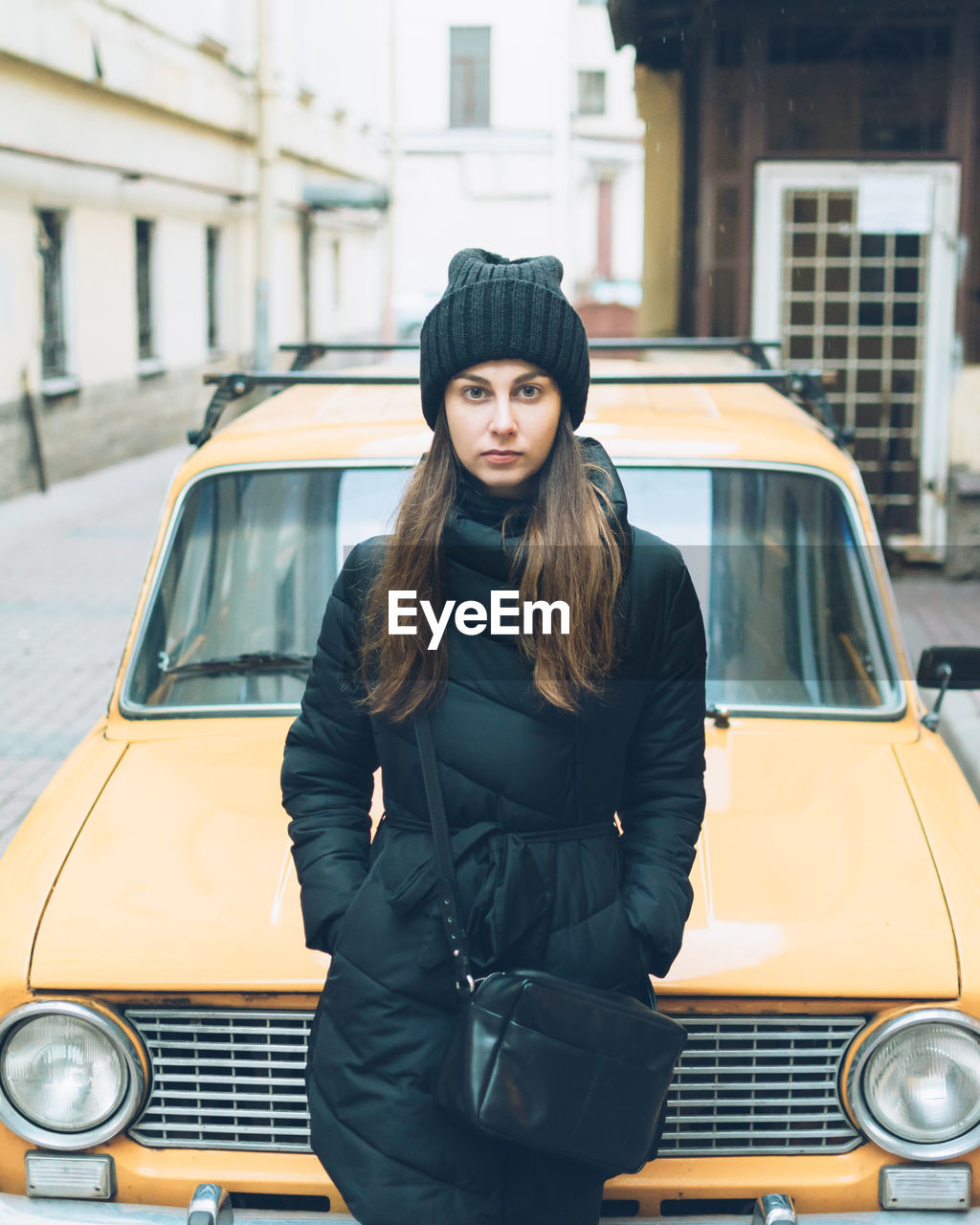 Portrait Of Beautiful Young Woman Leaning On Car Parked At Street