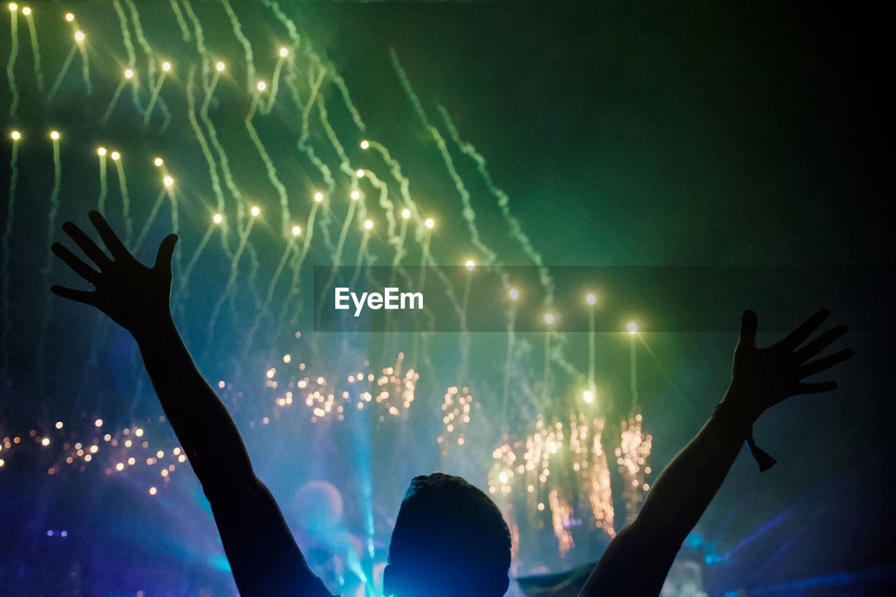 Silhouette Man With Arms Raised Enjoying Firework Display At Night