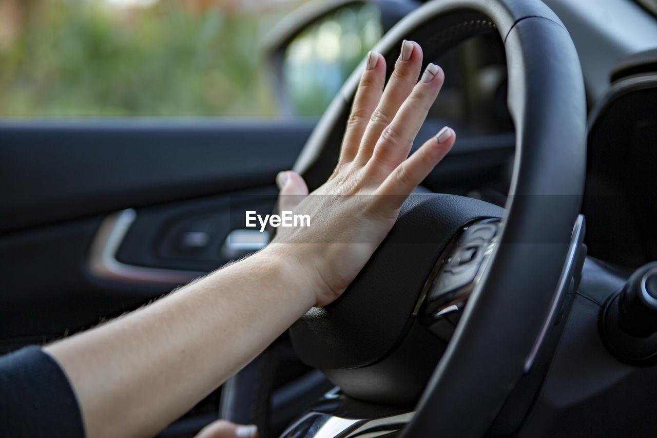 Hand presses the horn on the steering wheel of a modern car, no face person