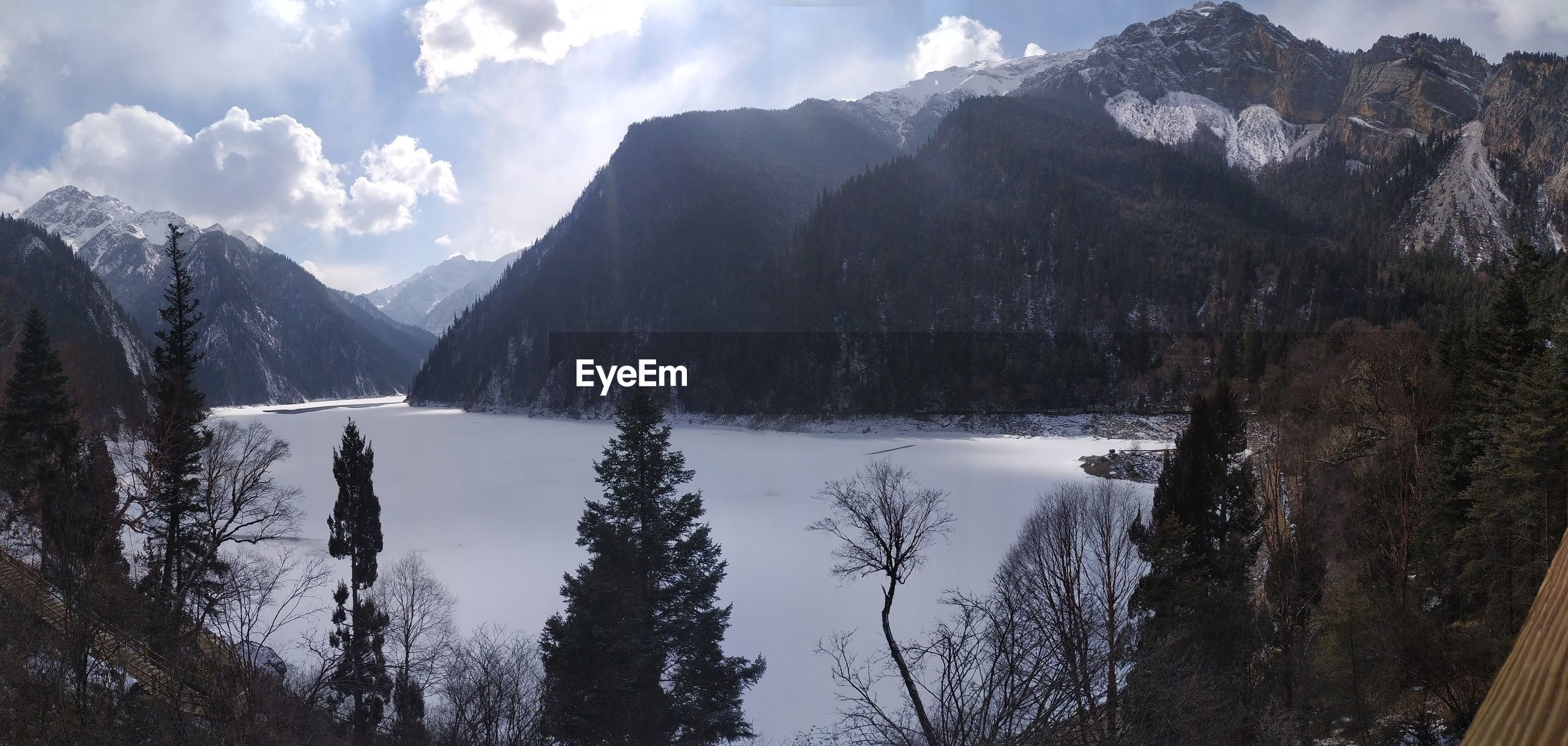 SCENIC VIEW OF MOUNTAINS AND RIVER AGAINST CLOUDY SKY