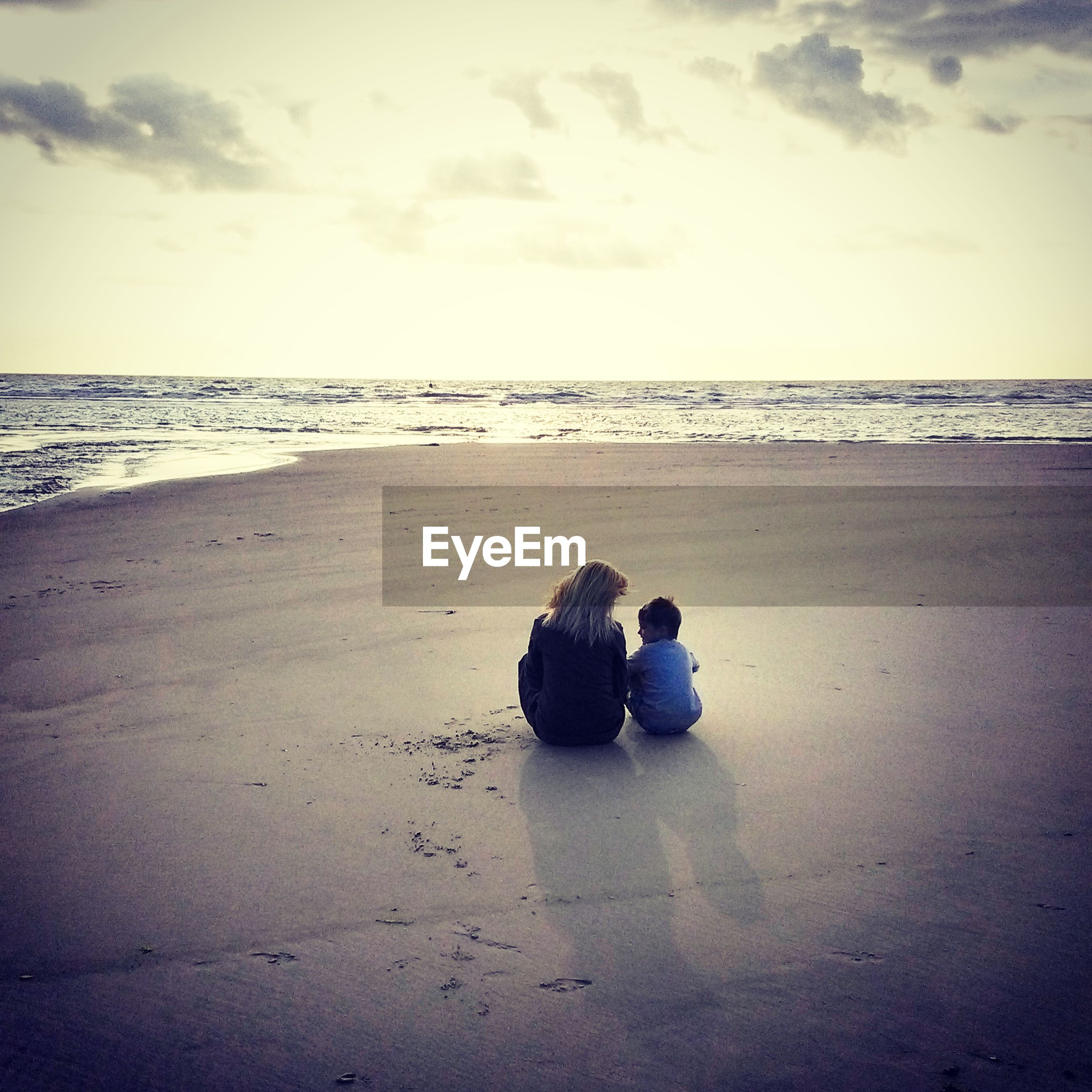 Rear view of mother and son sitting on sea shore at beach against sky