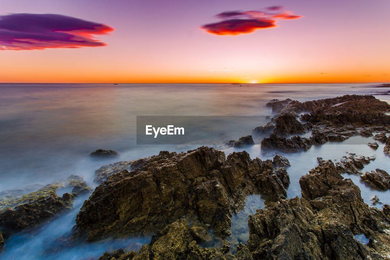 sea, sunset, sky, water, scenics - nature, beauty in nature, horizon over water, rock, horizon, orange color, rock - object, solid, motion, beach, nature, tranquil scene, no people, tranquility, land, power in nature