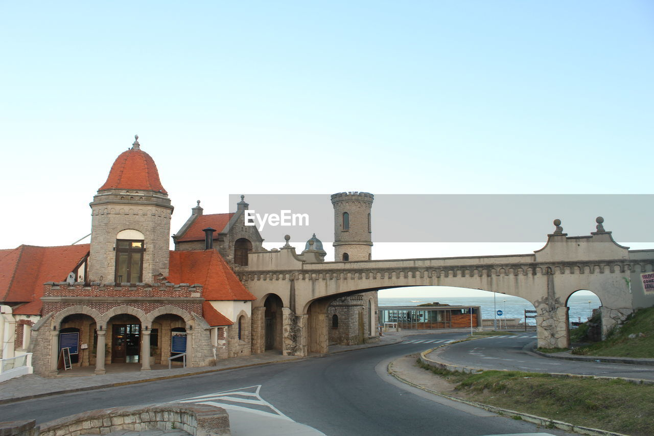 architecture, built structure, clear sky, transportation, sky, road, arch, building exterior, copy space, city, nature, building, connection, travel, history, the way forward, direction, the past, place of worship, no people, outdoors