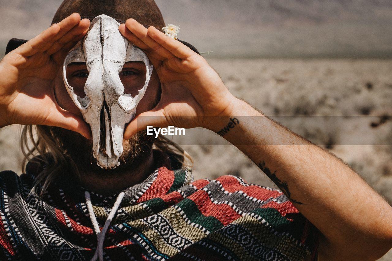 Portrait Of Man Holding Animal Skull