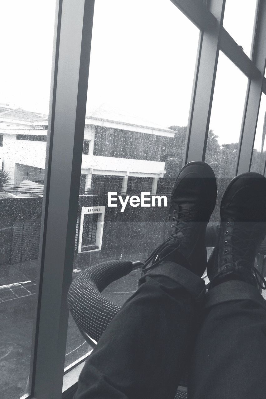 window, shoe, real people, one person, low section, human leg, personal perspective, indoors, day, lifestyles, train - vehicle, human body part, sitting, men, looking through window, standing, relaxation, close-up, one man only, sky, adult, people