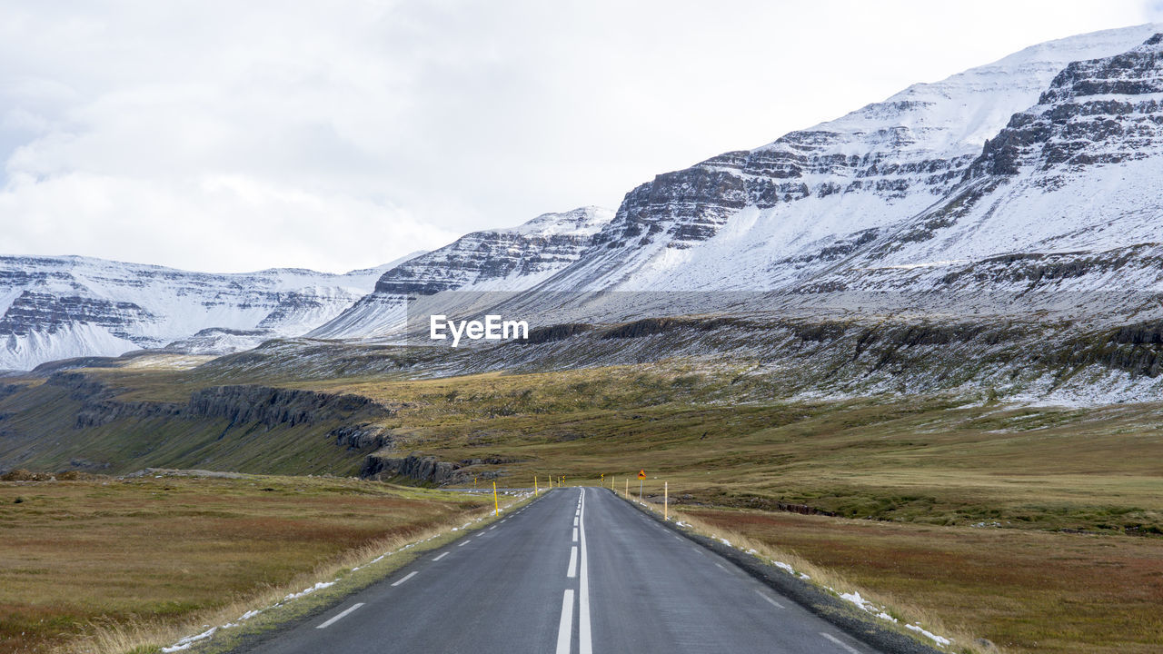 road, mountain, transportation, direction, the way forward, sky, environment, scenics - nature, landscape, snow, beauty in nature, nature, mountain range, diminishing perspective, no people, non-urban scene, cold temperature, country, day, outdoors, snowcapped mountain, dividing line, formation