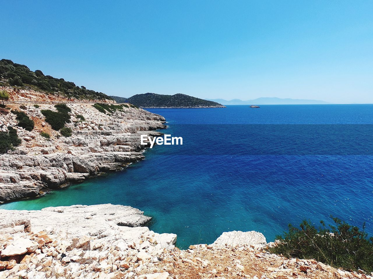 water, scenics - nature, sky, sea, beauty in nature, blue, tranquil scene, tranquility, clear sky, nature, land, day, copy space, idyllic, rock, mountain, beach, rock - object, no people, horizon over water, outdoors, rocky coastline, turquoise colored
