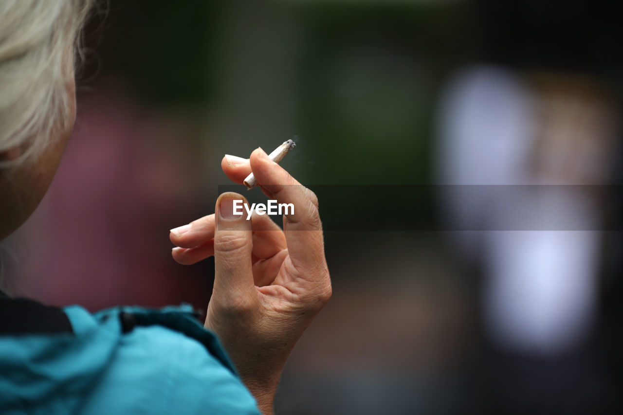 Cropped Image Of Person Holding Cigarette