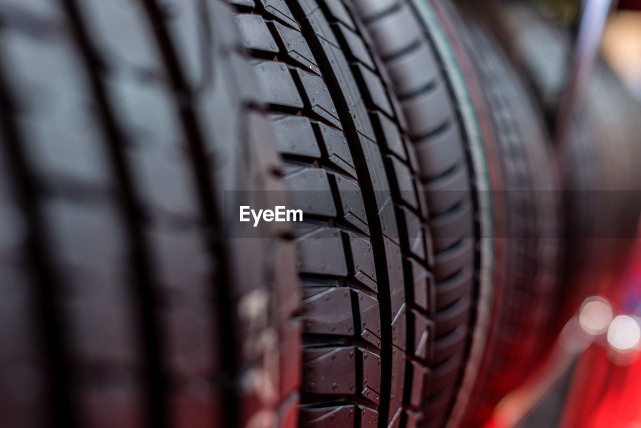 selective focus, wheel, tire, close-up, rubber, transportation, pattern, no people, mode of transportation, metal, land vehicle, black color, bicycle, sport, indoors, large group of objects, retail, in a row, day, full frame