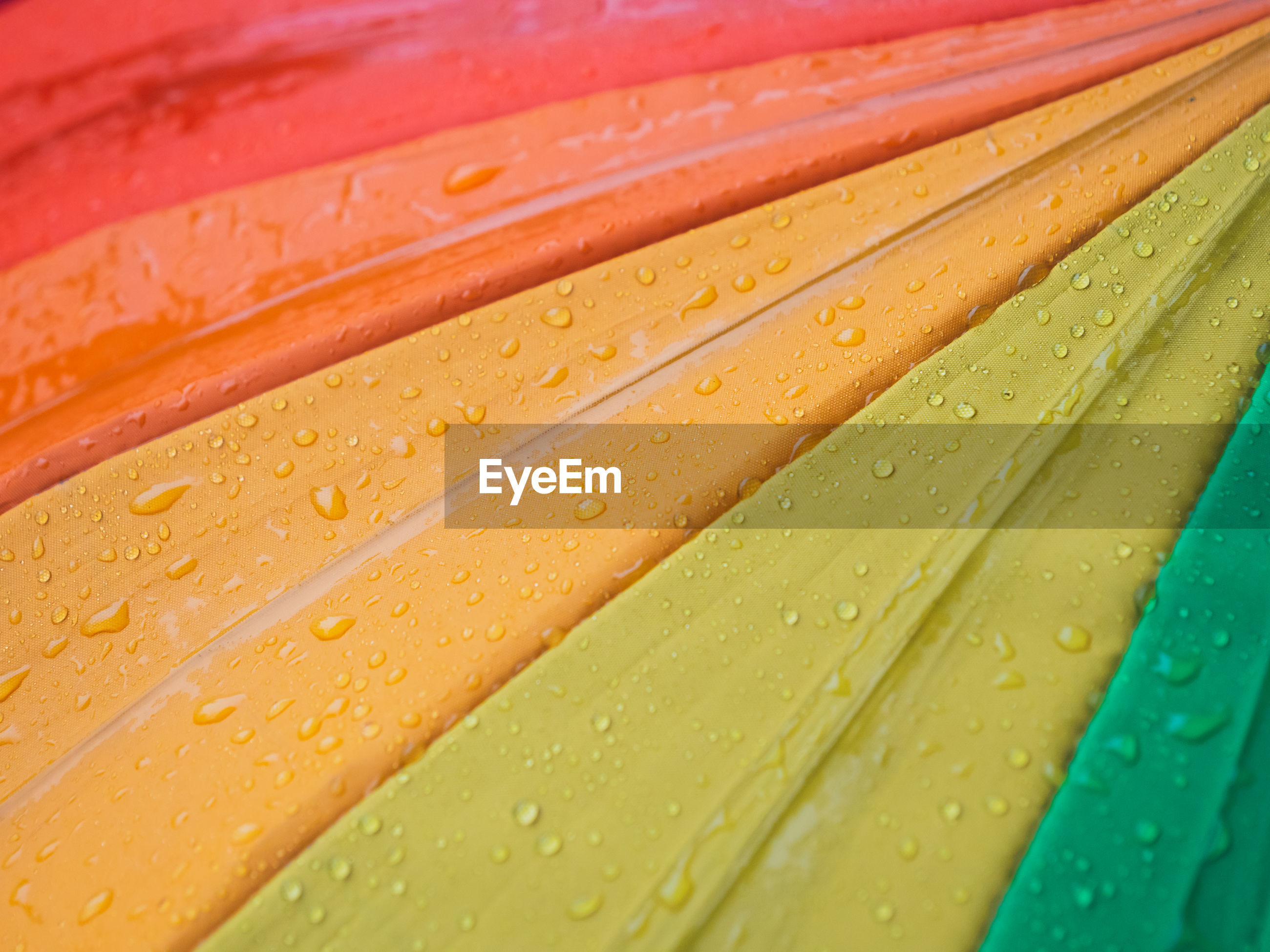 Close-up of colorful umbrellas and raindrops, top view