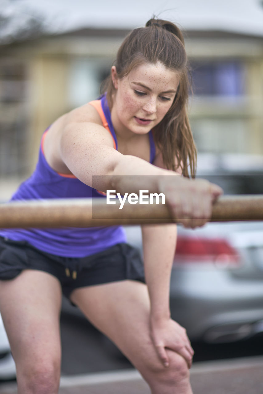 Woman Exercising By Railing On Road