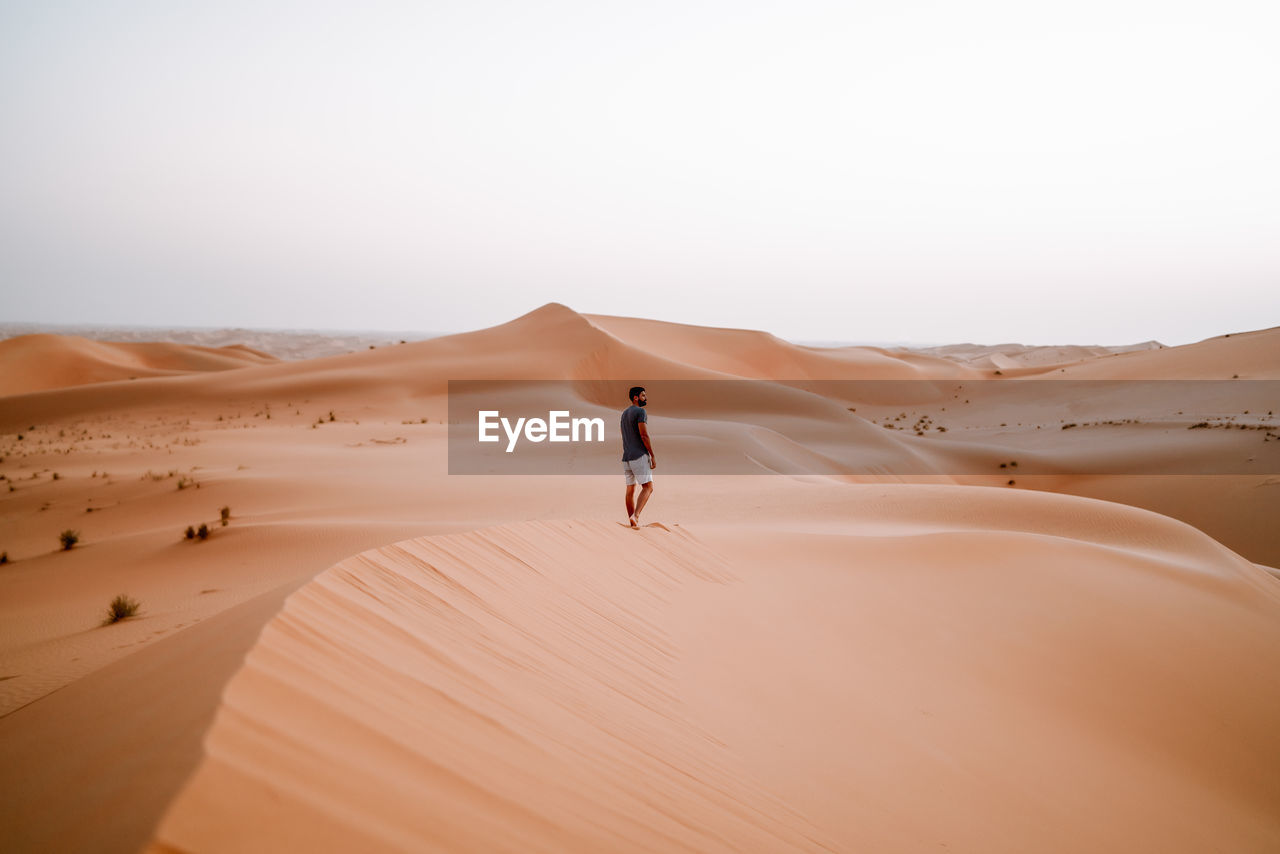 Man standing at desert against clear sky